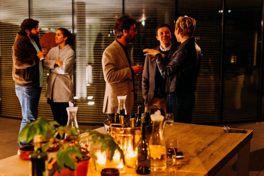 Five people standing and talking while drinking wine Photo by Antenna on Unsplash